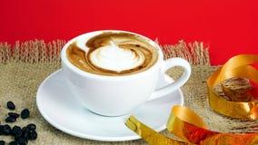 Schale Latte-, Cappuccino- oder Espressokaffee mit Milch setzte an den roten Hintergrund mit dunklen Röstkaffeebohnen Stockfoto