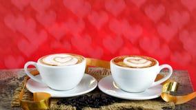 Schale Latte-, Cappuccino- oder Espressokaffee mit Milch setzte an eine hölzerne Tabelle mit dunklen Röstkaffeebohnen Stockfotografie