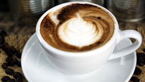 Schale Latte-, Cappuccino- oder Espressokaffee mit Milch setzte an eine hölzerne Tabelle mit dunklen Röstkaffeebohnen Stockbilder