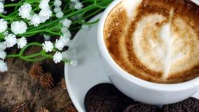 Schale Latte-, Cappuccino- oder Espressokaffee mit Milch setzte an eine hölzerne Tabelle mit dunklen Röstkaffeebohnen Stockbild