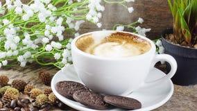 Schale Latte-, Cappuccino- oder Espressokaffee mit Milch setzte an eine hölzerne Tabelle mit dunklen Röstkaffeebohnen Lizenzfreie Stockfotos