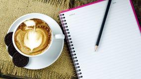 Schale Latte-, Cappuccino- oder Espressokaffee mit Milch setzte an eine hölzerne Tabelle mit dunklen Röstkaffeebohnen Stockfotos