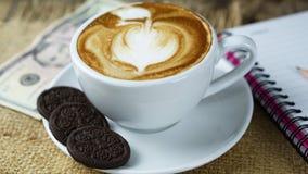 Schale Latte-, Cappuccino- oder Espressokaffee mit Milch setzte an eine hölzerne Tabelle mit dunklen Röstkaffeebohnen Lizenzfreie Stockbilder