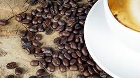 Schale Lattekaffee mit Milch setzte an eine hölzerne Tabelle mit dunklen Röstkaffeebohnen Lizenzfreies Stockfoto