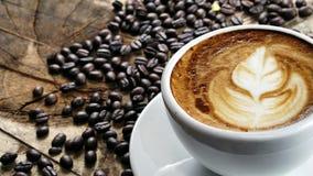 Schale Lattekaffee mit Milch setzte an eine hölzerne Tabelle mit dunklen Röstkaffeebohnen Stockfotos