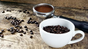 Schale Lattekaffee mit Milch setzte an eine hölzerne Tabelle mit dunklen Röstkaffeebohnen Lizenzfreies Stockbild