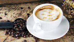 Schale Lattekaffee mit Milch setzte an eine hölzerne Tabelle mit dunklen Röstkaffeebohnen Lizenzfreie Stockfotos
