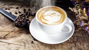 Schale Lattekaffee mit Milch setzte an eine hölzerne Tabelle mit dunklen Röstkaffeebohnen Stockfotografie