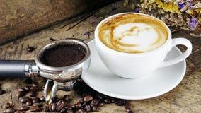 Schale Lattekaffee mit Milch setzte an eine hölzerne Tabelle mit dunklen Röstkaffeebohnen Stockbilder