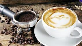 Schale Lattekaffee mit Milch setzte an eine hölzerne Tabelle mit dunklen Röstkaffeebohnen Stockfoto