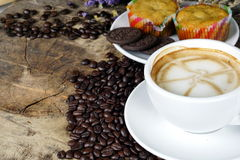 Schale Lattekaffee mit Milch setzte an eine hölzerne Tabelle mit dunklen Röstkaffeebohnen Lizenzfreie Stockfotografie