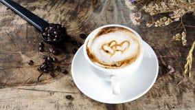 Schale Lattekaffee mit Milch setzte an eine hölzerne Tabelle mit dunklen Röstkaffeebohnen Lizenzfreie Stockbilder