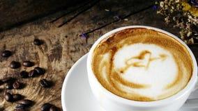 Schale Lattekaffee mit Milch setzte an eine hölzerne Tabelle mit dunklen Röstkaffeebohnen Stockbild