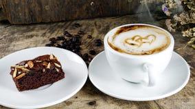 Schale Lattekaffee mit Milch setzte an eine hölzerne Tabelle mit dunklen Röstkaffeebohnen und Schokoladenschokoladenkuchen Lizenzfreie Stockfotografie
