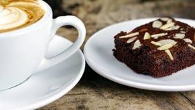 Schale Lattekaffee mit Milch setzte an eine hölzerne Tabelle mit dunklen Röstkaffeebohnen und Schokoladenschokoladenkuchen Lizenzfreies Stockbild
