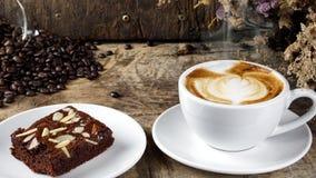 Schale Lattekaffee mit Milch setzte an eine hölzerne Tabelle mit dunklen Röstkaffeebohnen und Schokoladenschokoladenkuchen Stockfotografie