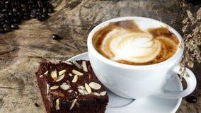 Schale Lattekaffee mit Milch setzte an eine hölzerne Tabelle mit dunklen Röstkaffeebohnen und Schokoladenschokoladenkuchen Stockbilder