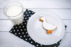 Schale Milch und Ingwer duckshape Plätzchen auf einem weißen Holztisch und dunkelblaues naplin mit Sternen Lizenzfreies Stockbild