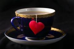 Schale mit einem Schatten in Form des Herzens und eines Herzens auf einem Thread Stockbilder