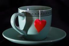 Schale mit einem Schatten in Form des Herzens und eines Herzens auf einem Thread Lizenzfreies Stockbild