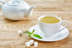 Schale mit grünem Tee und Teekanne auf weißem Holztischhintergrund Stockbilder