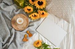 Schale mit heißem Cappuccino, graue woolen Pastelldecke, Sonnenblumen, Schlafzimmer lizenzfreies stockfoto