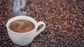 Schale mit heißem Kaffee auf Röstkaffeebohnen Langsame Bewegung stock footage