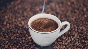 Schale mit heißem Kaffee auf Röstkaffeebohnen Langsame Bewegung stock video