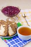 Schale mit heißem Tee, Kuchen und Vase mit dem Kochen Stockfotografie