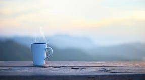 Schale mit Kaffee auf Tabelle über Bergen gestalten landschaftlich Stockfotografie