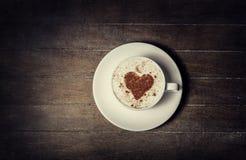 Schale mit Kaffee und Form des Kakaoherzens auf ihm. Lizenzfreie Stockfotos