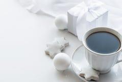 Schale mit Kaffee, weißer Geschenkbox, Plätzchen und Weihnachtsbällen, hallo Stockfotos