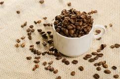 Schale mit Kaffeebohne auf traditionellem Sackgewebe Stockbild