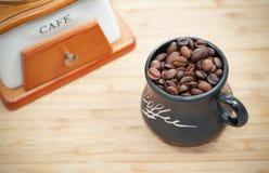 Schale mit Kaffeebohnen auf hölzernem Hintergrund mit Schleifer stockfoto