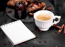 Schale mit schwarzem Kaffee und einem leeren Papiernotizbuch Stockfoto