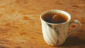 Schale mit Tee auf einem Holztisch stock video