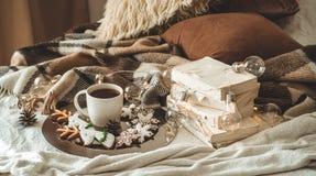 Schale mit Tee oder Kaffee, Tannenzweig, Plätzchen in Form der Schneeflocken, gemütliche gestrickte Decke, Baumwolle und gemütlic lizenzfreie stockfotografie
