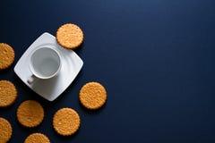 Schale mit Tee und Keksen auf einem dunkelblauen Hintergrund Stockfotos