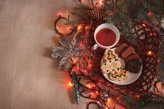 Schale Plätzchen des schwarzen Tees und des Schokoladensplitters mit Tannenbaum verzweigt sich mit Weihnachtsgirlande Stockfotos