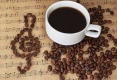 Schale schwarzer Kaffee auf Noten mit Zimt und Bohnen Stockbilder