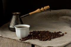 Schale schwarzer Kaffee, Brauentopf und Kaffeebohnen Lizenzfreie Stockfotografie