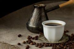 Schale schwarzer Kaffee, Brauentopf und Kaffeebohnen Stockbild