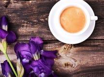 Schale schwarzer Kaffee mit einem Blumenstrauß der blauen Iris Stockbilder