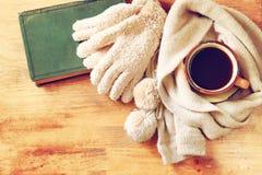 Schale schwarzer Kaffee mit einem warmen Schal und einem alten Buch auf hölzernem Hintergrund filreted Bild Stockbilder