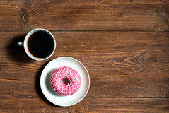 Schale schwarzer Kaffee mit rosa Donut auf hölzernem Hintergrund, Draufsicht Stockfotos