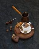 Schale schwarzer Kaffee mit Schokoladenkeks-, -Zimtstange- und -rohrzuckerwürfeln auf rustikalem hölzernem Brett über dunklem Ste Stockfotografie