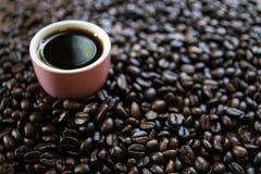 Schale schwarzer Kaffee und Kaffeebohnen auf hölzernem Hintergrund Stockfoto