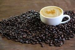 Schale schwarzer Kaffee und Kaffeebohnen auf hölzernem Hintergrund Stockbild