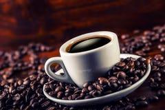 Schale schwarzer Kaffee und verschüttete Kaffeebohnen Stockfotos