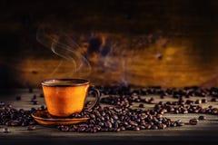 Schale schwarzer Kaffee und verschüttete Kaffeebohnen Süßes Hörnchen und ein Tasse Kaffee im Hintergrund Stockbild